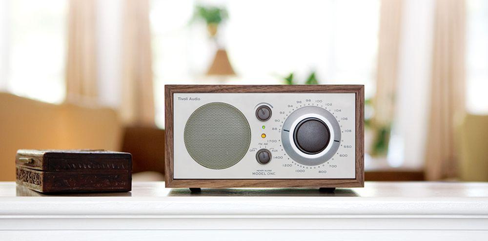 ''Radio AM/FM avec haut-parleur longue portée !''  Issu du brillant esprit du célèbre ingénieur du son Henry Kloss, la TIVOLI Model One® est une radio de salon qui souhaite allier beau son et plaisir radiophonique. Pour cela cette radio s'incarne dans un boîtier en bois fabriqué à la main représentant le coffret idéal pour une véritable enceinte acoustique sans résonnance. Cela tombe bien car son haut-parleur de 3 pouces longue portée à blindage magnétique connecté à un circuit de traitement de la fréquence capable d'ajuster le son sur plus d'une demi-octave. Il permet d'obtenir un équilibre sonore précis même dans le registre des graves. Vous serez surpris des qualités acoustiques de cette radio qui propose un tuner AM/FM analogique capable de capter les stations au signal même le plu faible.  De plus, on note la présence d'une prise jack pour y brancher une antenne AM et FM externe.  ''Design rétro et moderne séduisant !''  La radio AM/FM TIVOLI Model One séduira tant l'oreille que le regard grâce à un design alliant efficacement modernité et vintage. Son boîtier en bois de grande qualité fabriqué à la main, sa mollette de syntonisation analogique 5.1, ses boutons de volume et de sélection de signal ; tout se marie parfaitement à l'ensemble pour un rendu esthétique qui a sa place tant au bureau qu'à la maison. Du côté de la connectique, Tivoli et Kloss optent principalement sur l'efficacité. En plus de la prise jack pour brancher une antenne externe, la Model One® offre également une entrée auxiliaire, une sortie casque et une sortie enregistrement. Il est difficile de rester de marbre face à cette radio de salon qui existe dans plusieurs coloris avec différents niveaux de finition avec ses gammes Frost White Collection ou encore Platinum.  Cobra a aimé : Le niveau de qualité tan pour la partie audio que la partie esthétique.